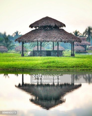 Reflection Of Thatched Roof Shade In Pond