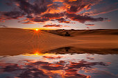 Reflection of the sunset sky and sand dunes in the water.