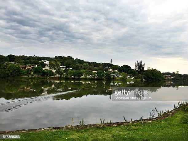 Reflection Of Trees On River Against Cloudy Sky