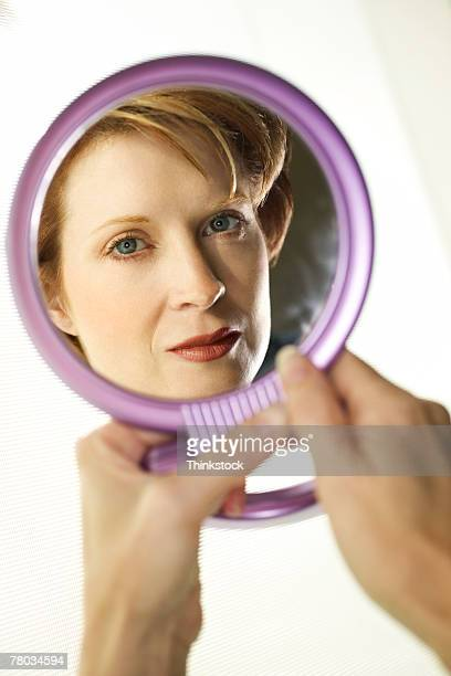Reflection of woman in hand mirror