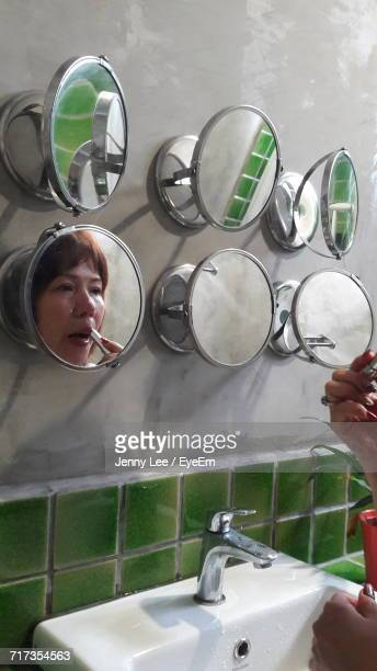 Reflection Of Woman In Mirror Applying Lipstick On Lips