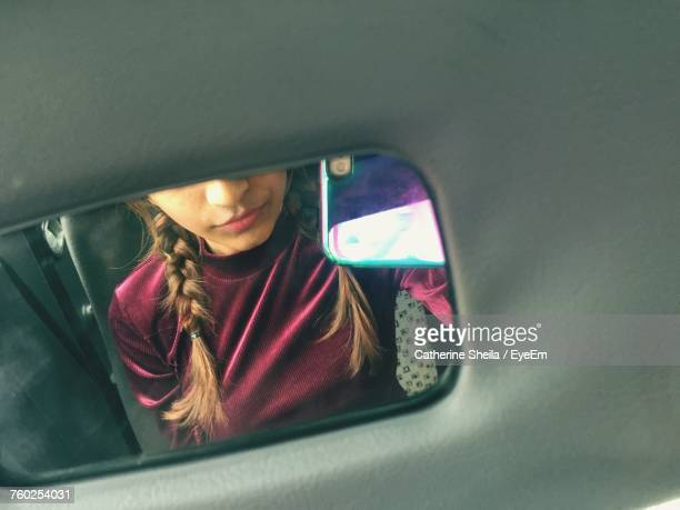 Reflection Of Woman In Mirror Of Car