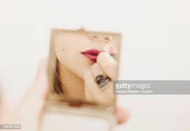 Reflection Of Woman In Mirror While Applying Lipstick Against White Background