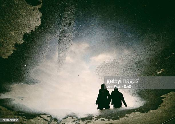 Reflection Of Young Couple In Puddle