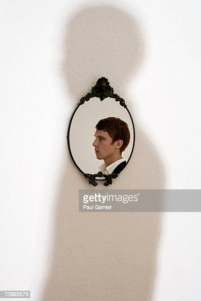 Reflection of young man in ornate mirror on wall