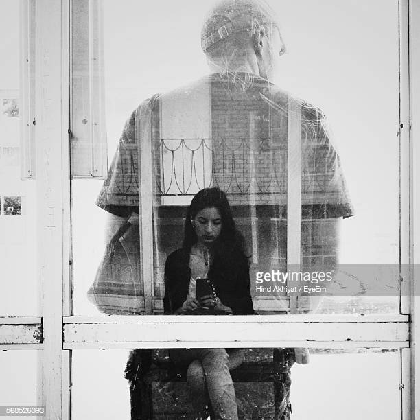 Reflection Of Young Woman With Mobile Phone In Front Of Man