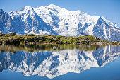 Reflection on crystal clear alpine lake, running man