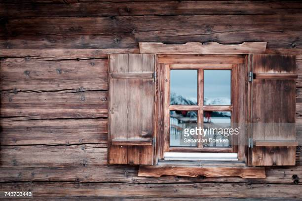 Reflection on glass window of log cabin, Kufstein, Tyrol, Austria