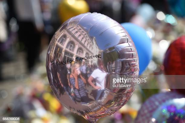 A reflection on the surface of a balloon shows a woman covering her eyes with a handkerchief as she pauses at the floral tributes gathered in St...