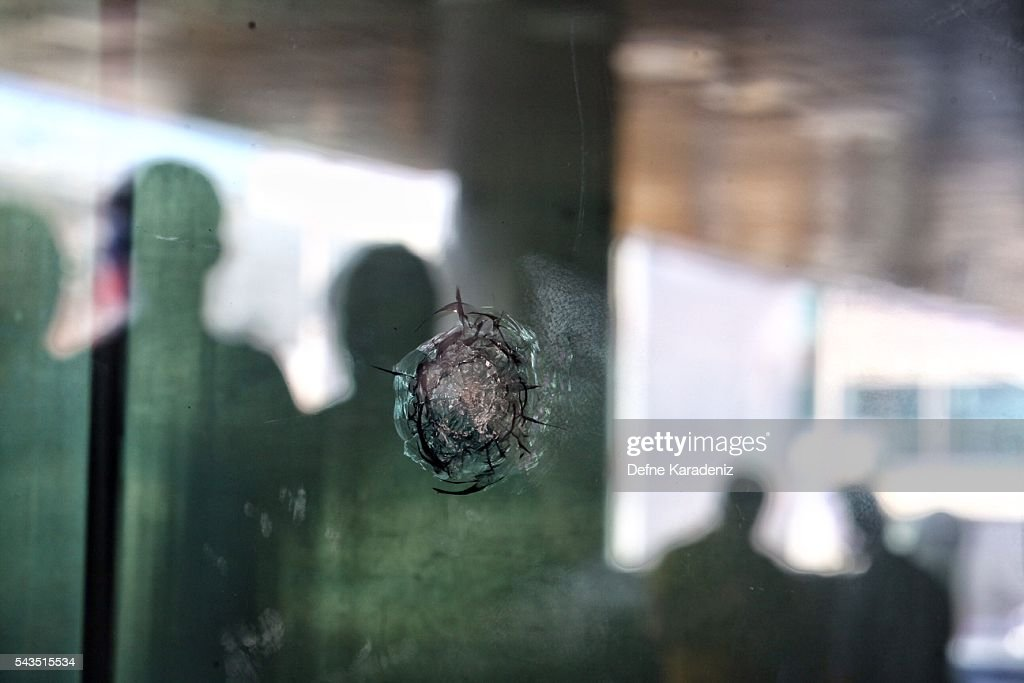 Reflections are cast on the glass where bullet holes remain at Turkey's largest airport, Istanbul Ataturk, Turkey, June 29, 2016, Turkey. Three suicide bombers opened fire before blowing themselves up at the entrance to the main international airport in Istanbul yesterday, killing at least 36 people and wounding 147 people according to PM Binali Yildirim.
