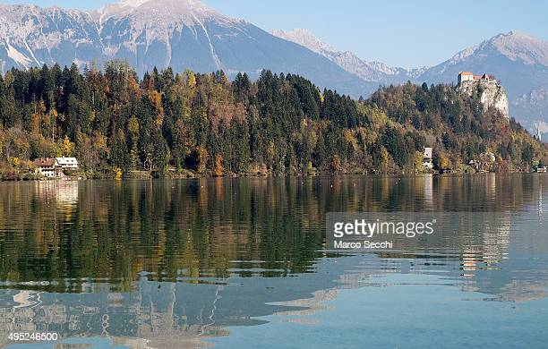 Reflections of autumn foliage and the Castle on Bled Lake on November 1 2015 in Bled Slovenia Bled Lake in the Julian Alps is known as one of the...