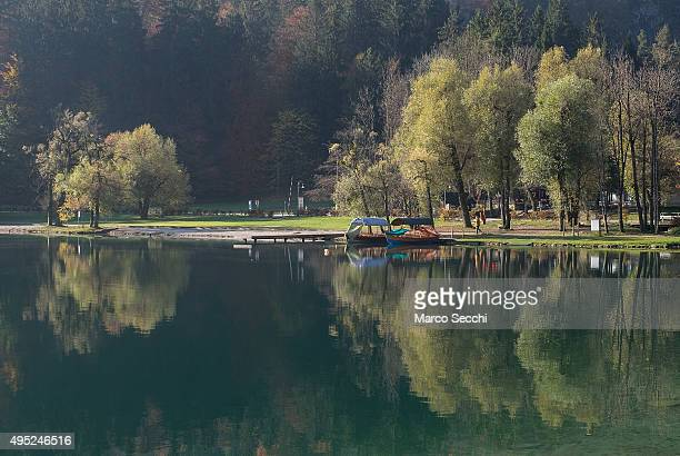 Reflections of autumn foliage on Bled Lake on November 1 2015 in Bled Slovenia Bled Lake in the Julian Alps is known as one of the most enchanted...