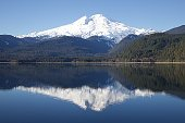 The remote east side of Mt. Baker is reflected in Baker Lake on a cold winter morning.