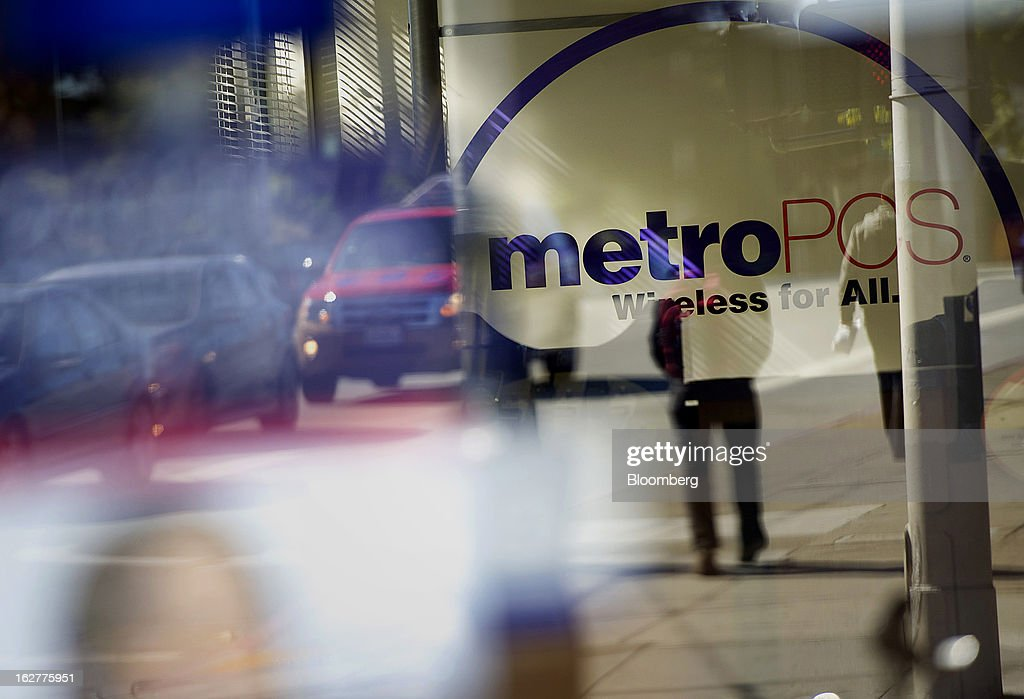 Reflections of pedestrians are seen in the window of a MetroPCS Communications Inc. store in San Francisco, California, U.S., on Tuesday, Feb. 26, 2013. MetroPCS Communications Inc. fourth-quarter revenue, released today, matches estimated earnings. Photographer: David Paul Morris/Bloomberg via Getty Images