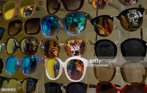 Reflections of tourists are seen on sunglasses as they shop inside a store in Shanghai on August 14 2017 China's industrial output a key engine of...