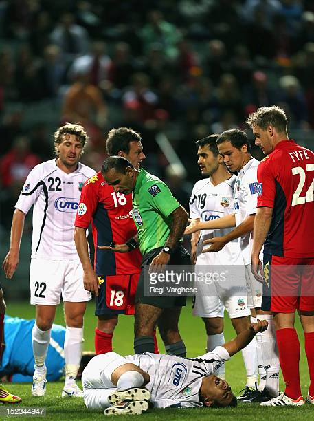 Refree Abdullah Mohammed Al Hilalo looks at Murzoev Kamoliddin of Bunyodkor who clashed with Adelaide goalkeeper Eugene Galekovic during the AFC...