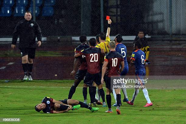 Refree Jarred Gaven Gillett shows the red card to Indian player Pritma Kotal as Guam's mid fielder Justin David cries in pain during the the Asia...