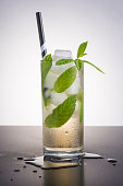 Refreshing cocktail with ice, mint leaves and a striped straw.