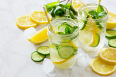 Refreshing summer drink with lemon and cucumber on a background of stone. The concept of eating vegetarians, fresh vitamins, a homemade refreshing fruit drink.