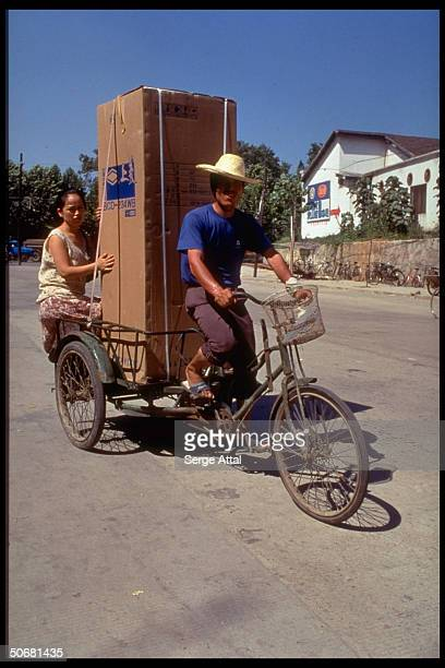 Refrigerator being delivered on bicycle
