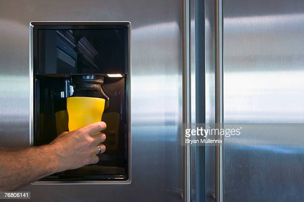 Refrigerator, ice and water dispenser and a man holding a cup