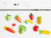 collection of magnets fridge in the form of fruit and vegetables placed on refrigerator door