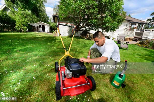 Refueling, maintenance / mowing the lawn in nice green garden.