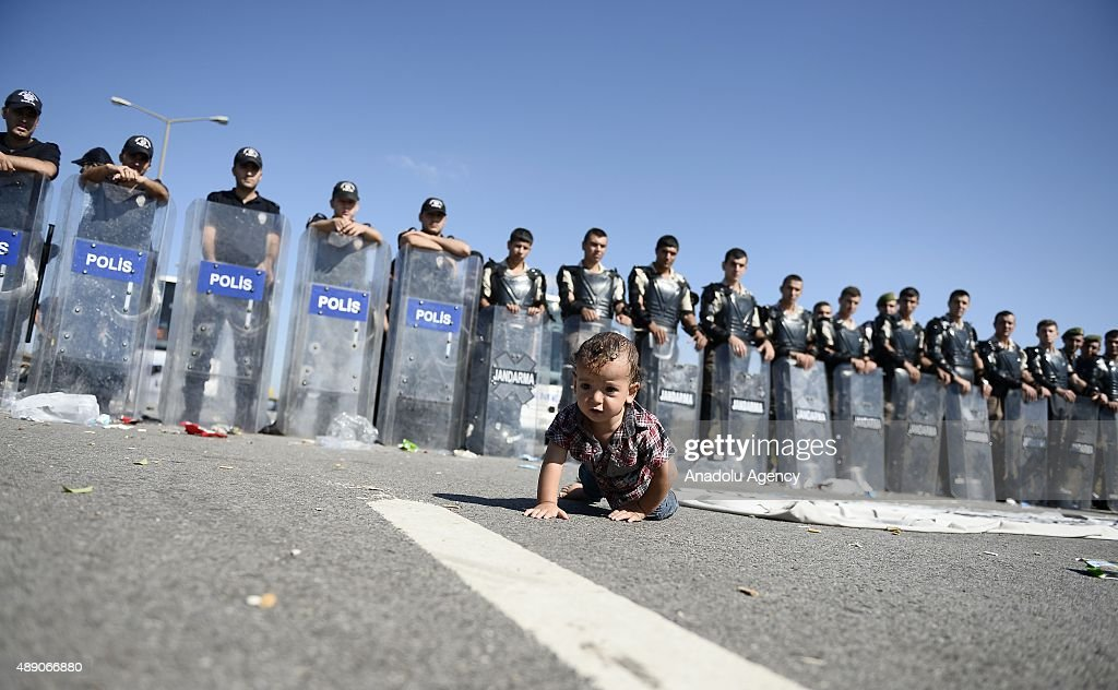 A refugee baby crawls in front of the Turkish police and the gendarme forces on TEM highway in Edirne, Turkey on September 19, 2015. Turkish security forces stops the refugees on the way to the Edirne city center.