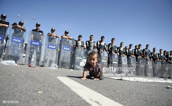 A refugee baby crawls in front of the Turkish police and the gendarme forces on TEM highway in Edirne Turkey on September 19 2015 Turkish security...