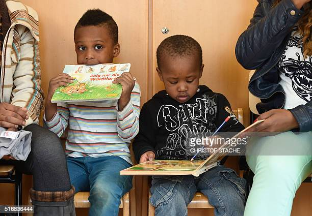 A refugee boy and his mother from Nigeria read books during a first event of the threeyear program 'reading start for refugee children' in the...
