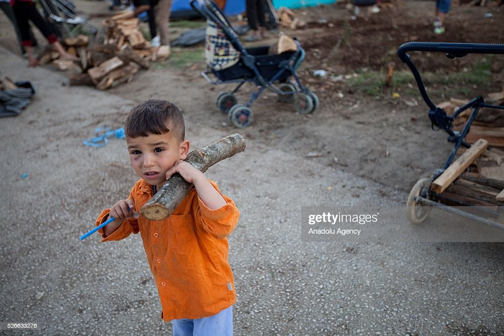 A refugee boy holds a wood distributed by volunteers at Idomeni refugee camp in Greece on April 30, 2016. Refugees' 'journey of hope' towards Western European countries where they dream of having a better life ends in the Balkans following the latest decision.