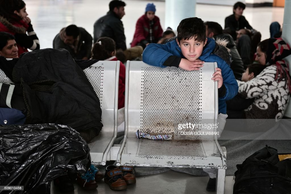 A refugee boy looks on from his shelter inside a passenger terminal at the port of Piraeus near Athens on Febuary 8, 2016 , where dozens of refugee and migrant families live temporarily, prior being able to travel towards the borders. Streams of people fleeing conflict or poverty continue to make the often perilous journey from Turkey across the Mediterranean and through the Balkans, despite cold winter weather, in the hope of starting new lives in more prosperous European countries / AFP / LOUISA GOULIAMAKI