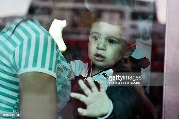 A refugee boy peers out from a bus taking them to the metro station after disembarking from the port of Piraeus from the Greek island of Kos on...