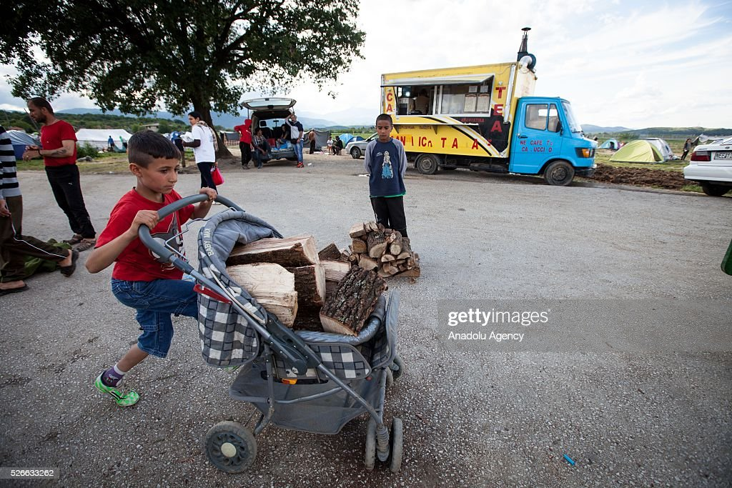 A refugee boy pushes a stroller loaded with the wood distributed by volunteers at Idomeni refugee camp in Greece on April 30, 2016. Refugees' 'journey of hope' towards Western European countries where they dream of having a better life ends in the Balkans following the latest decision.