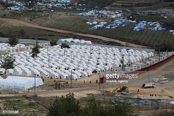 A refugee camp is seen as Turkish authorities build 35 kilometres long 3 metres high and 7 tones weighted concrete wall in order to prevent illegal...