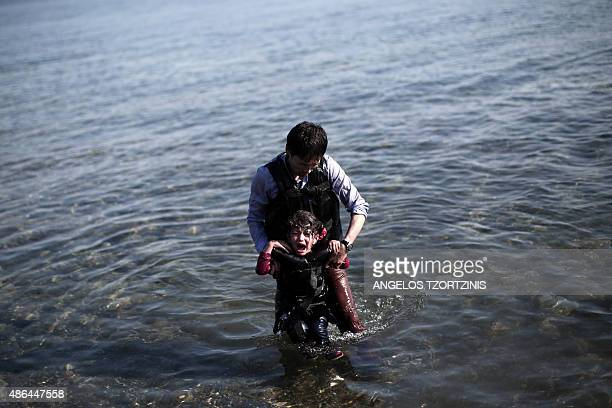 A refugee carries his child as he arrives on a shore of the Greek island Lesbos after arriving from Turkey in an inflatable boat on September 4 2015...