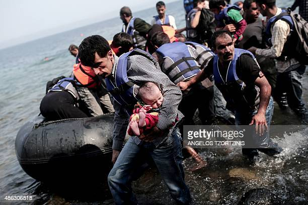 A refugee carries his child as they arrive on the shores of the Greek island Lesbos in an inflatable dingy across the Aegean Sea from from Turkey on...
