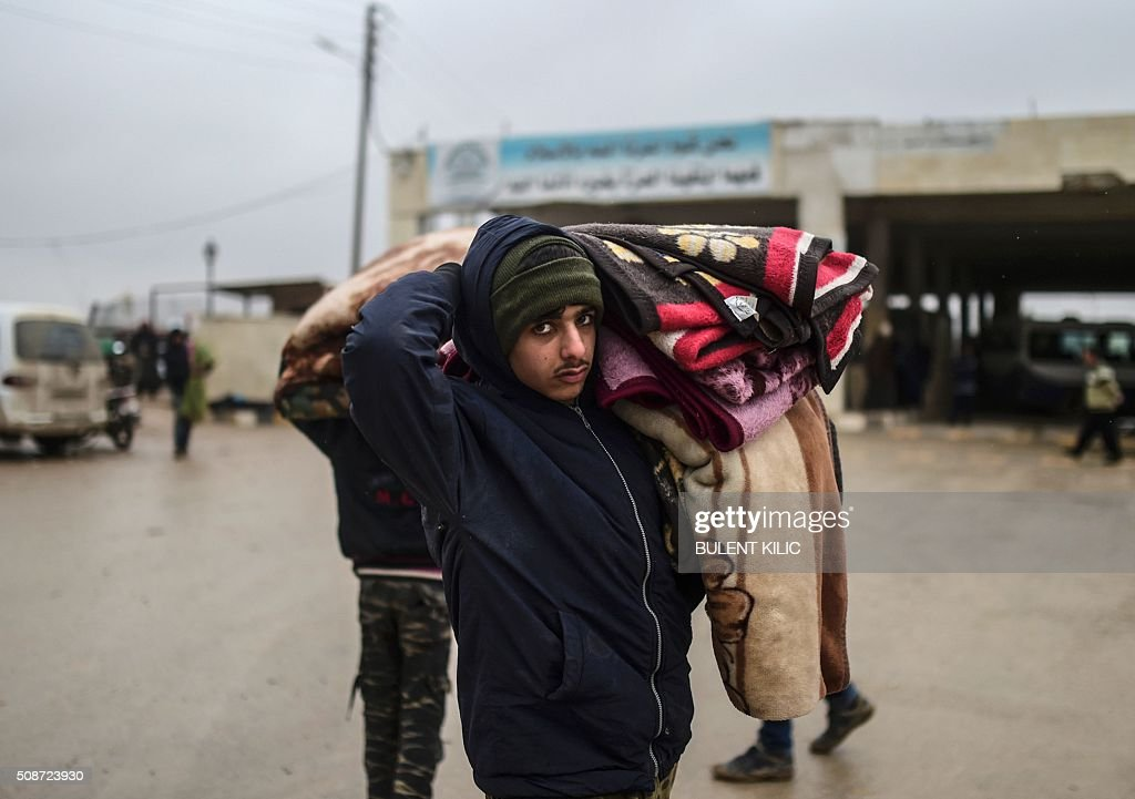 A refugee carrying belongings arrivea at the Turkish border crossing gate as Syrians fleeing the northern embattled city of Aleppo wait on February 6, 2016 in Bab-Al Salam, near the city of Azaz, northern Syria. Thousands of Syrians were braving cold and rain at the Turkish border Saturday after fleeing a Russian-backed regime offensive on Aleppo that threatens a fresh humanitarian disaster in the country's second city. Around 40,000 civilians have fled their homes over the regime offensive, according to the Syrian Observatory for Human Rights monitor. / AFP / BULENT KILIC