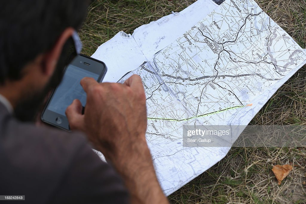 A refugee checks an iPhone and a map while stopping with other refugees and supporters for a rest in the hamlet of Neschholz during their protest march across nearly 600km from Wuerzburg to Berlin on October 2, 2012 near Bad Belzig, Germany. Approximately 25 refugees who are seeking political asylum are marching to protest the conditions under which they live in Germany. Asylum seekers in Germany are by law prohibited from working and their ability to travel is very restricted. The group expects to arrive in Berlin on October 6.