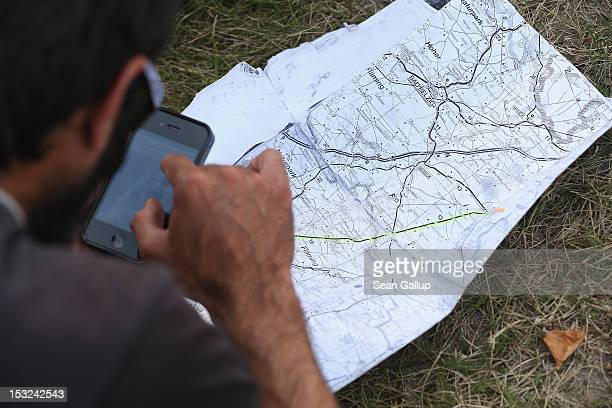 A refugee checks an iPhone and a map while stopping with other refugees and supporters for a rest in the hamlet of Neschholz during their protest...