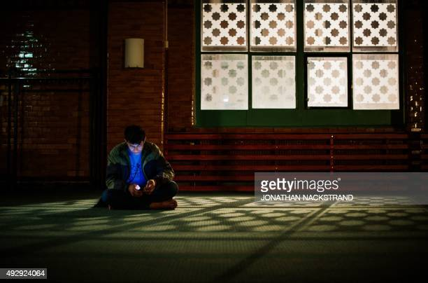 A refugee checks his cell phone at the prayer hall after arriving to Stockholm central mosque on October 15 2015 after many hours buss journey from...