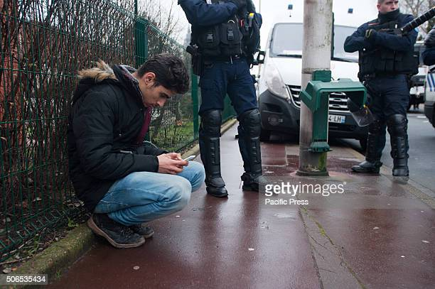 A refugee checks his phone with riot police men in the background at the refugees welcome march in solidarity with and by the refugees residing in...