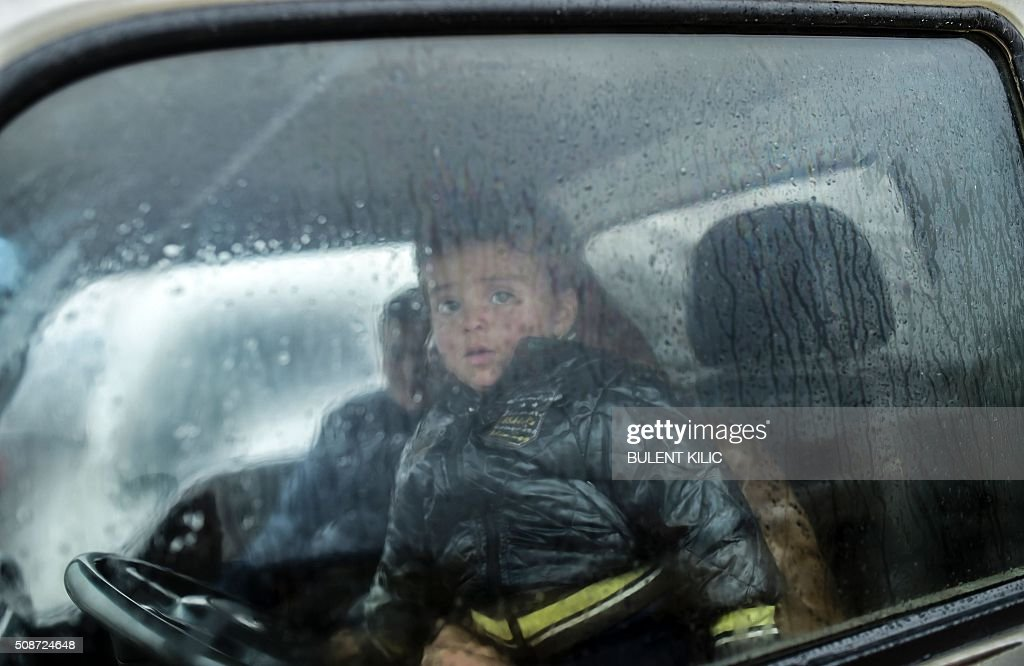 A refugee child is pictured inside a car near the Turkish border crossing gate as Syrians fleeing the northern embattled city of Aleppo wait on February 6, 2016 in Bab-Al Salam, near the city of Azaz, northern Syria. Thousands of Syrians were braving cold and rain at the Turkish border Saturday after fleeing a Russian-backed regime offensive on Aleppo that threatens a fresh humanitarian disaster in the country's second city. Around 40,000 civilians have fled their homes over the regime offensive, according to the Syrian Observatory for Human Rights monitor. / AFP / BULENT KILIC