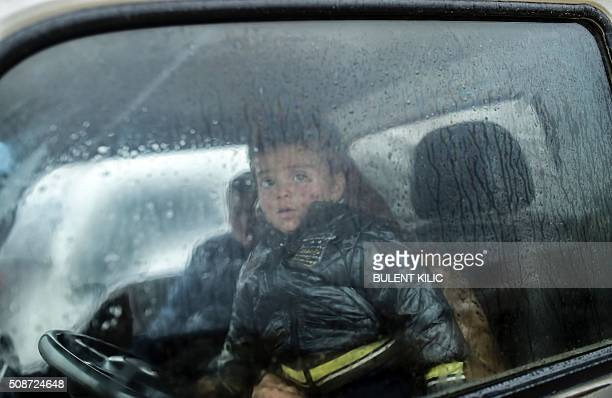 A refugee child is pictured inside a car near the Turkish border crossing gate as Syrians fleeing the northern embattled city of Aleppo wait on...