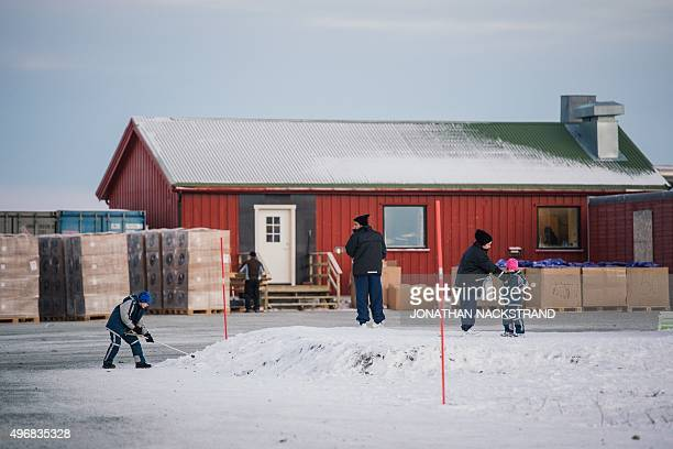 Refugee child plays with the snow as refugees gather in front of a residential container at the arrival centre for refugees near the town on Kirkenes...