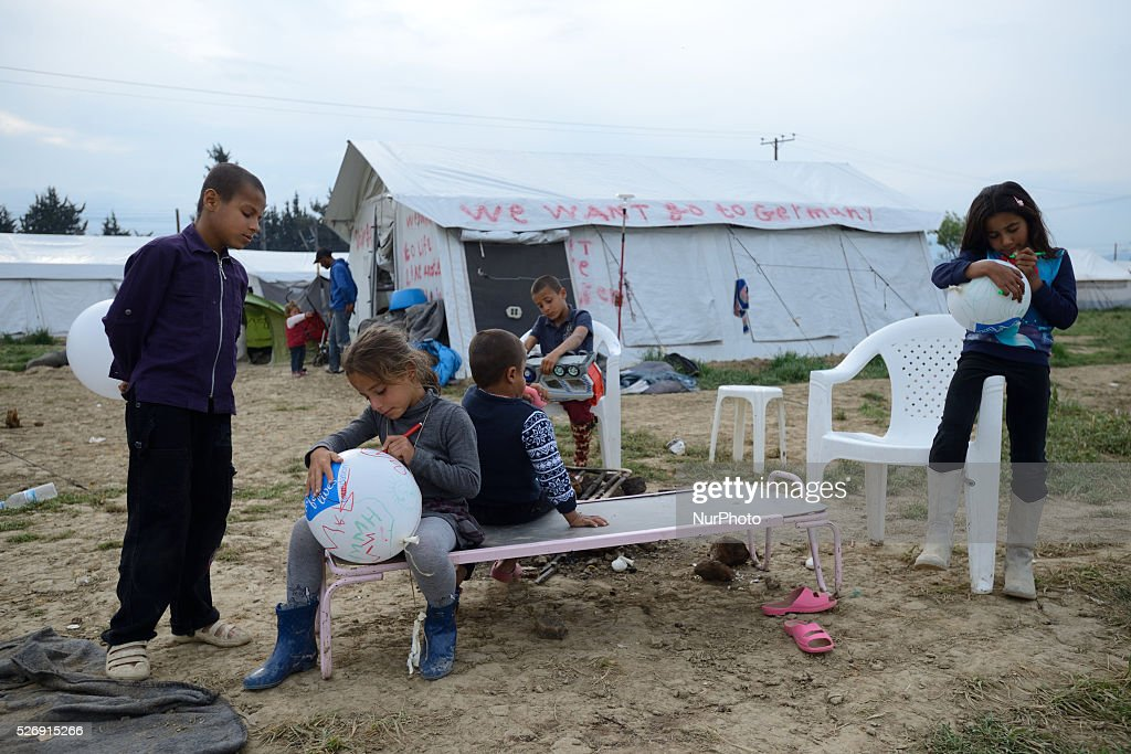 "Refugee children are playing near a tent painted with the slogan ""We want go to Germany"" on May 1'st, 2016 in Idomeni refugee camp. Humanitarian conditions in the camp are deteriorating as many thousands of migrants are still located in the makeshift refugee camp, located at the Greece-Macedonia border, waiting for the border to re-open."