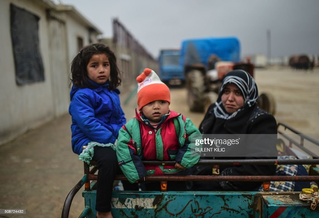 Refugee children arrive a the Turkish border crossing gate as Syrians fleeing the northern embattled city of Aleppo wait on February 6, 2016 in Bab-Al Salam, near the city of Azaz, northern Syria. Thousands of Syrians were braving cold and rain at the Turkish border Saturday after fleeing a Russian-backed regime offensive on Aleppo that threatens a fresh humanitarian disaster in the country's second city. Around 40,000 civilians have fled their homes over the regime offensive, according to the Syrian Observatory for Human Rights monitor. / AFP / BULENT KILIC