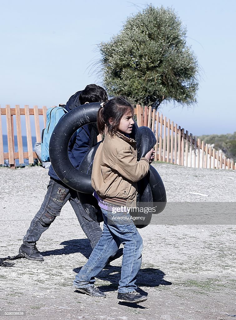 Refugee children carry flotation rings on the coast as Turkish gendarmerie captures around 700 refugees, who were trying to reach Lesbos Island of Greece, in operations conducted at 3 different bays, namely Pissa, Bahceli and Candarli, in Dikili district of Izmir, Turkey on February 8, 2016.