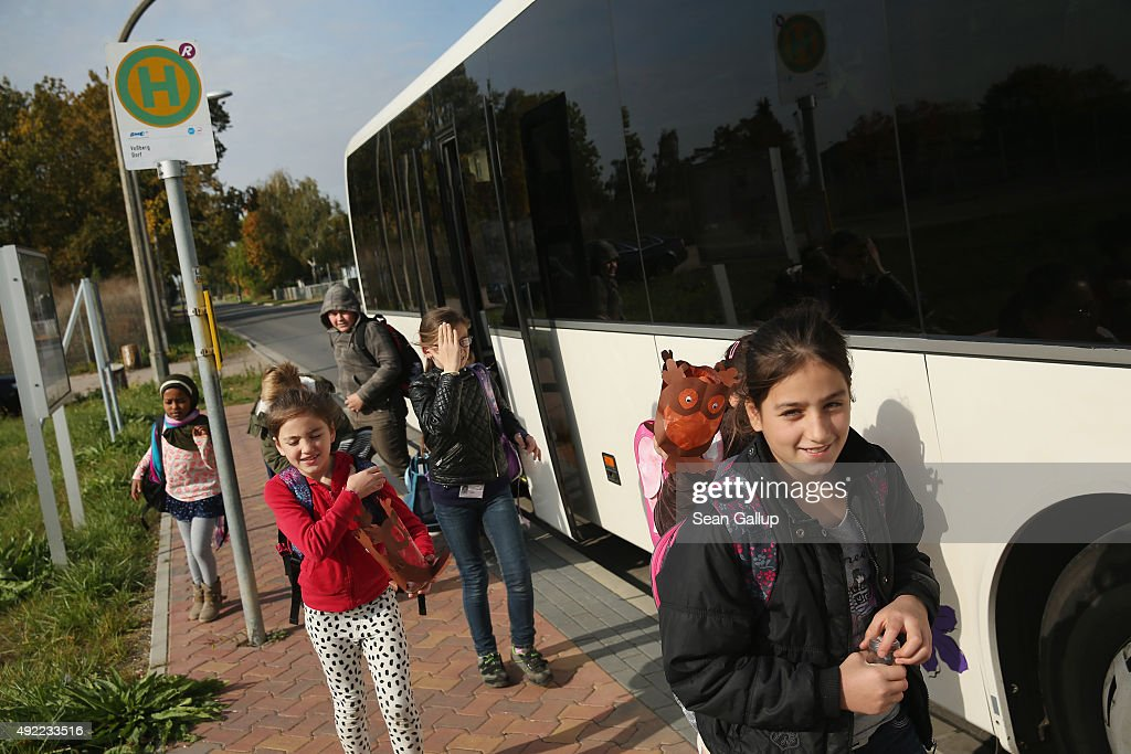 Refugee children descend from a bus as they return from school to the asylumseekers' shelter that is home to them and their families in Vossberg...