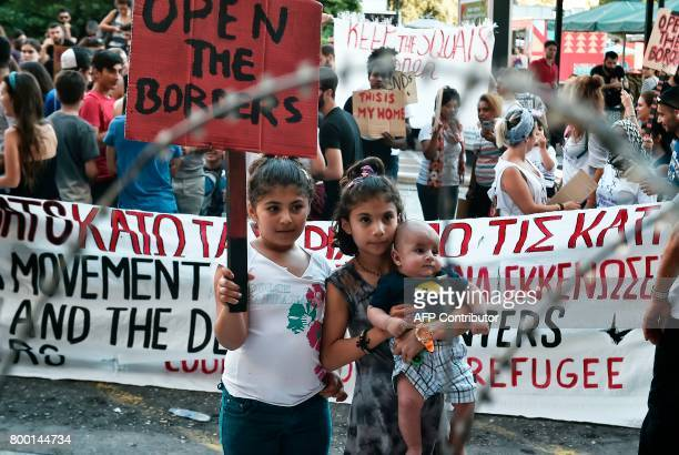 Refugee children hold up a placard reading 'Open the borders' as they stand behind a mock fence set up at the entrance to the Ministry of the...